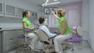 At a reception the dentist. Portrait of a dentist and a boy. Dentist shows a close-up of an x-ray picture of her teeth on the monitor