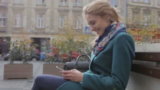 Attractive young woman using her touch screen mobile cell phone and smiling to herself