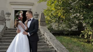 Beautiful bride and groom gently hugging and Kissing in the courtyard of the old castle