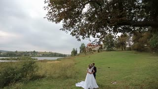 Beautiful bride and groom gently hugging in a grass near the lake and the old castle.