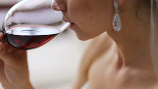 Beautiful bride drinking red wine.
