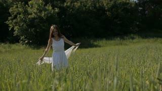 Beautiful girl having fun outdoors in the field. Slow motion. Happy smiling young woman enjoying nature. Freedom concept.young Beautiful woman walking among the field.