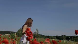 Beautiful girl having fun outdoors in the poppies field. Slow motion. Happy smiling young woman enjoying nature. Freedom concept.young Beautiful woman walking among blooming poppy flowers.