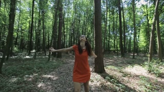 beautiful girl in a red dress walking through the forest.Slow motion