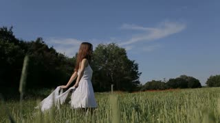 Beautiful girl in white dress having fun outdoors in the field. Slow motion. Happy smiling young woman enjoying nature. Freedom concept.young Beautiful woman walking among the field.