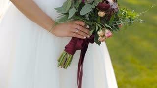 Beautiful wedding bouquet in hands of bride.Bride holds a wedding bouquet in her hands.