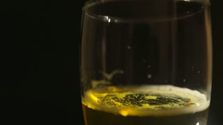 Beer poured in glass with bubbles on black background