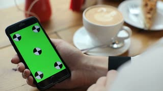 Businesswoman using mobile cell phone with green touch screen in cafe