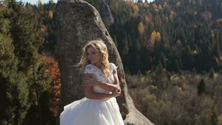 Charming bride posing for photos in the mountains