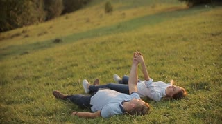 Charming couple in love and lie on the grass in the mountains on sunset