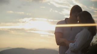 Charming couple in love have fun and hugging in the mountains on sunset