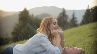 Charming couple in love have fun and lie on the grass in the mountains on sunset