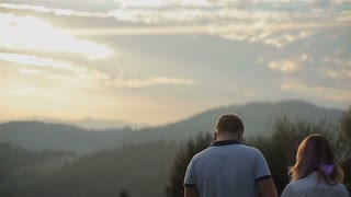 Charming couple in love hugging and walking in the mountains on Beautiful sunset