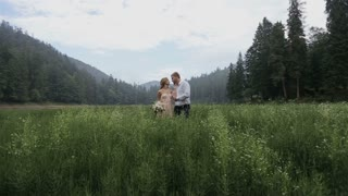 Charming couple in love hugging in the grass on the mountains background