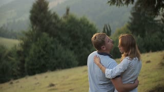 Charming couple in love hugging in the mountains on sunset