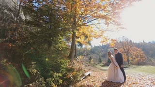 Charming couple in love - pretty girl in light dress and handsome man hugging in the autumn forest