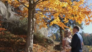 Charming couple in love - pretty girl in light dress and handsome man hugging in the autumn forest.fall leaves