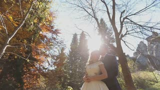 Charming couple in love - pretty girl in light dress and handsome man hugging in the forest on the sunset