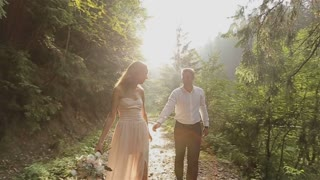 Charming couple in love - pretty girl in light dress and handsome man walking in the forest on the sunset