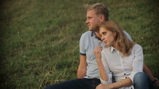 Charming couple in love sitting on the grass and hugging in the mountains on sunset