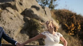 Charming wedding couple running in the mountains