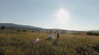 Charming wedding couple running on the field in the mountains