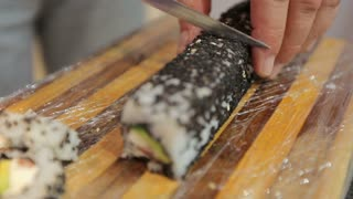 chef in restaurant preparing and Cutting sushi rolls healthy food