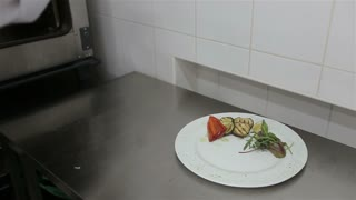 chef puts the finished steak on a plate,dish presentation