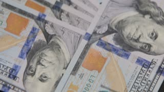 close up dolly shot of scattered American paper money bills. Cash money background. Benjamin Franklin portrait on 100 US dollar bill close up