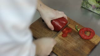 Close up of a chef slicing a red bell pepper on a wooden cutting board.Close-up of chef hands cooking and preparing food in restaurant  kitchen