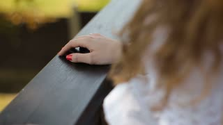 Close up of a woman's hands on a railing next to a lake in park in slow motion.Close up of a young woman's hands on a banister next to lake
