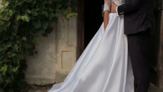 Close-up of Beautiful bride and groom gently hugging in the courtyard of the old castle.