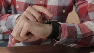 Close up of young man using smartwatch while sitting in cafe