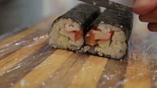 Close-up Sushi chef cutting sushi rolls