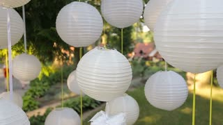 Closeup Beautiful decor for a party of white paper Chinese lanterns hanging in a tree.
