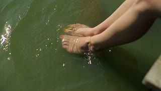 Closeup girl splashed feet on wooden bridge.Girl Sitting on a Pier Looking at the Waves
