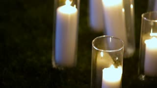 Closeup Romantic burning white candles in glass vases standing on a grass for an evening wedding ceremony.