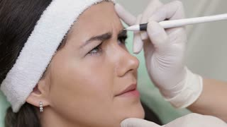 Cosmetologist prepares woman face to botox injections