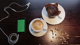 Cup of coffe with marshmellou and cellphone with green in cafe