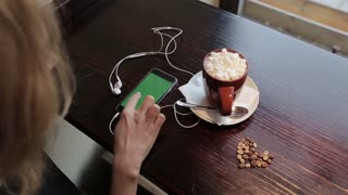 Cup of coffe with marshmellou and women using cellphone with green in cafe