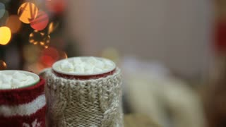 Cups of hot cocoa with marshmallow with Christmas decorations at home, Christmas tree on background, cozy mood