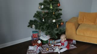 cute baby sitting at christmas tree at home and playing with christmas decoration