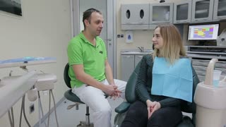 Dental care and hygiene, portrait of adult caucasian dentist at work and smiling at camera with customer sitting on exam chair