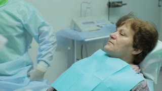 Elderly woman having her teeth fixed at dentist office