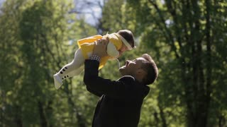 Father playing with young daughter in the backyard. Baby have fun