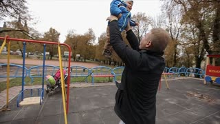 Father playing with young son at a playground.father throws the son upwards