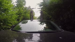 Front view. Car rides on a forest road with bikes on the roof