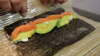 Hands make long sushi roll. Rice with pieces of fish. Sushi chef demonstrating skill. Famous japanese dish.