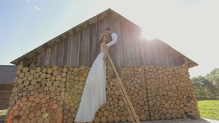 Happy bride and groom standing on ladder near wooden ambar at the wedding walk