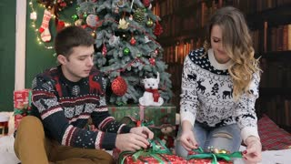 Happy couple, sitting near the new year tree and tying bow on Christmas gift Birthday gift present or New Year present.